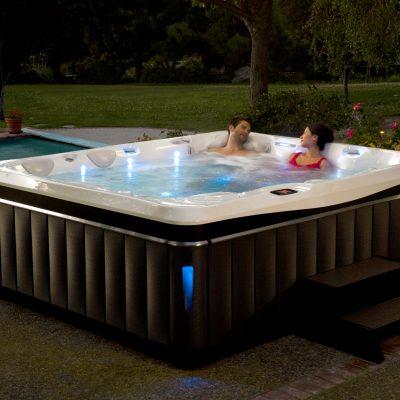 Two people using Caldera Utopia spa at night