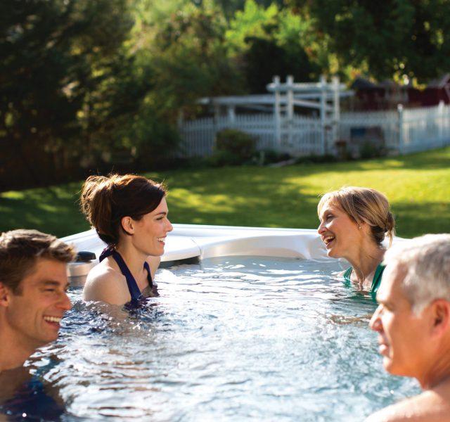 Four people enjoying Caldera spa paradise medium hot tub