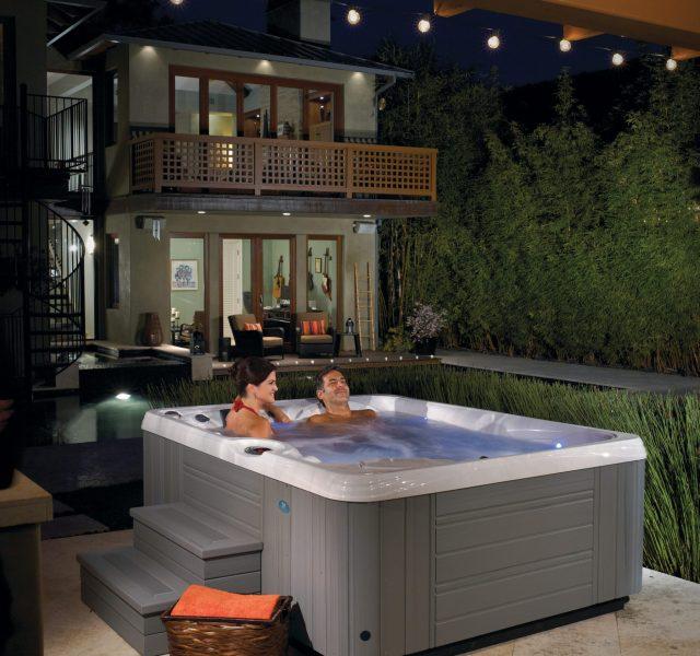 Two people enjoying Caldera gray small hot tub spa outdoors