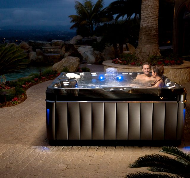 Two people sat in Caldera Utopia hot tub spa in landscaped garden