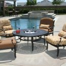 Four patio chairs surround metal table with ice bucket in centre