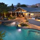 Landscaped backyard with swimming pool, outdoor kitchen and patio furniture