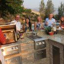 Friends enjoying alfresco dinner around outdoor kitchen