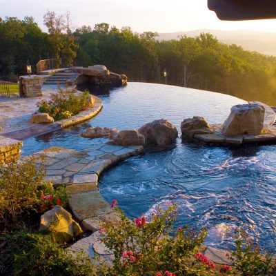 Infinity pool in landscaped garden at sunset