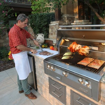 man cooking on alfresco kitchen grill outdoors
